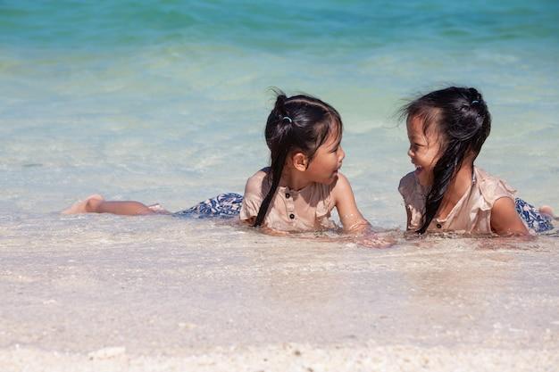 Twee leuke aziatische kindmeisjes die pret hebben om water in het mooie overzees samen te spelen