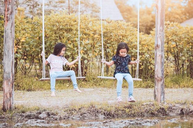 Twee leuke aziatische kindmeisjes die schommeling samen in het landbouwbedrijf spelen bij platteland met pret
