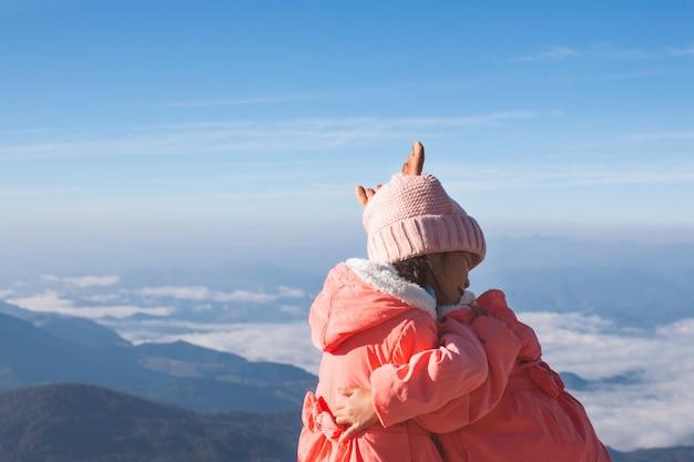 Twee leuke aziatische kindmeisjes die sweater en warme hoed dragen die samen koesteren