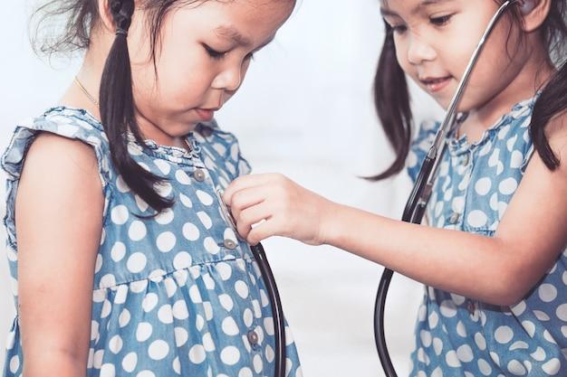 Twee leuke aziatische kleine kindmeisjes die arts en patiënt met stethoscoop samen spelen