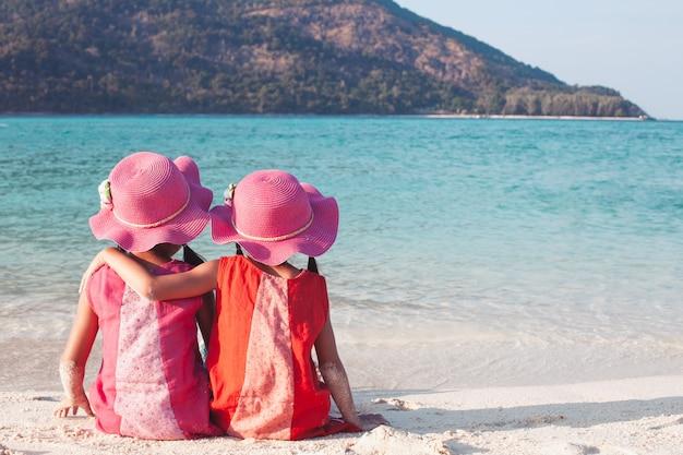 Twee leuke aziatische kleine kindmeisjes die en elkaar op het strand zitten koesteren