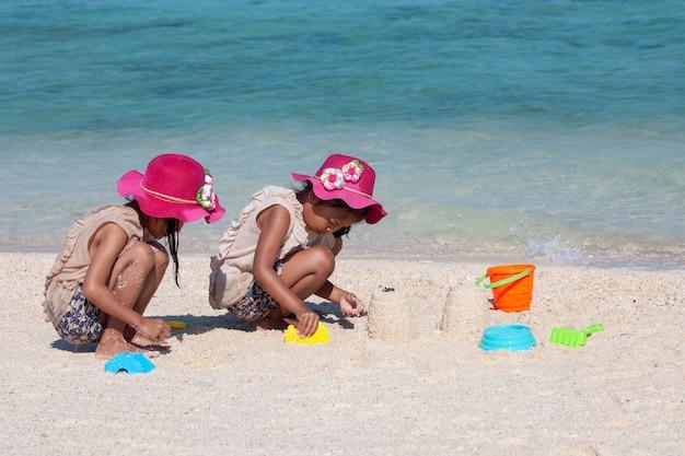 Twee leuke aziatische kleine kindmeisjes die en samen met zand op het strand zitten spelen