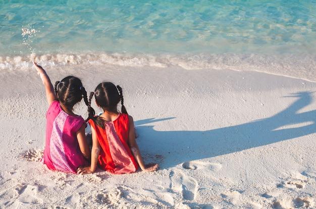 Twee leuke aziatische kleine kindmeisjes die en samen op het strand zitten spelen