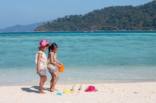 Twee leuke aziatische kleine kindmeisjes die met zand samen op het strand dichtbij het mooie overzees spelen