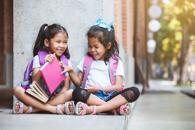 Twee leuke aziatische leerlingsmeisjes die een boek samen in de school met pret en geluk lezen