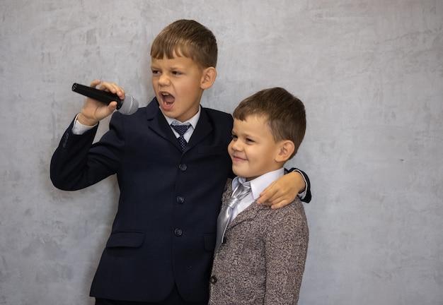 Twee leuke jongens spelen met vocale microfoon die populaire zangers kopiëren
