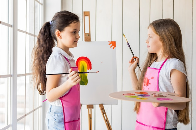 Twee leuke meisjes die op het canvas schilderen die elkaar bekijken