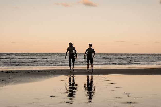 Twee lichamelijk fitte jonge mannen die in zwarte wetsuits met planken in de schemering de zee in lopen