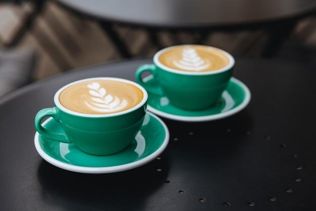 Twee lichtblauwe kopjes gevuld met aroma koffie op zwarte tafel