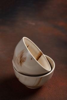 Twee lichte handgemaakte kopjes op een bruine tafel