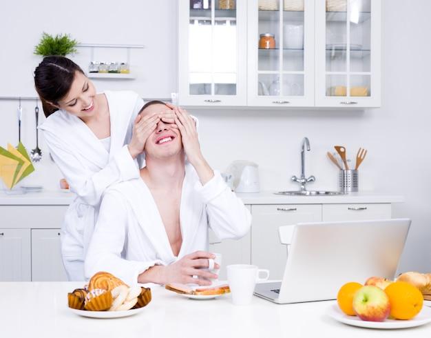 Twee liefdevolle flirtende mensen met laptop in de keuken