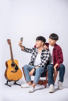 Twee liefdevolle jonge mannen zitten op een stoel en maken een selfie vanaf een smartphone.