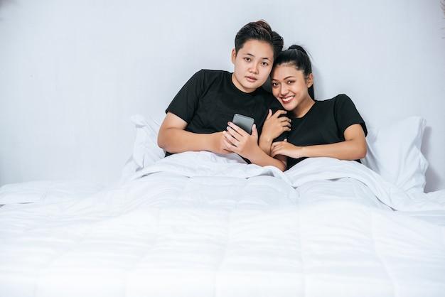 Twee liefdevolle vrouwen die slapen en smartphones spelen.