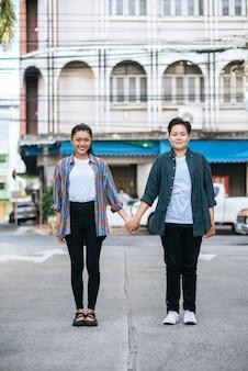 Twee liefdevolle vrouwen staan en hand in hand op straat.