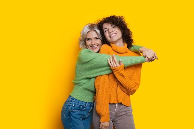 Twee lieve blanke vrouwen met krullend haar poseren gelukkig op een gele muur met vrije ruimte omarmen