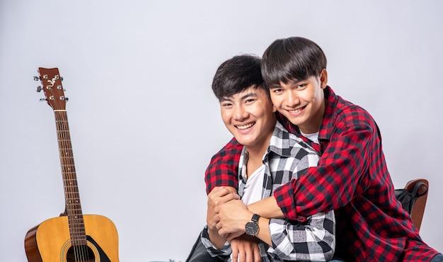 Twee lieve jongemannen zaten knuffelend in een stoel en met een gitaar ernaast.