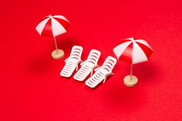 Twee ligstoelen en rode parasols op een rode achtergrond. ruimte kopiëren.