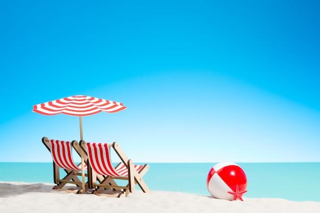 Twee ligstoelen met parasol en strandbal aan de kust