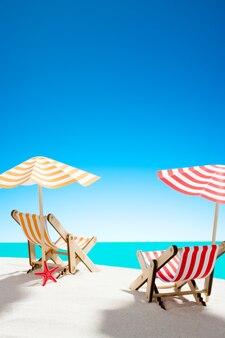 Twee ligstoelen onder een parasol op het zandstrand aan zee
