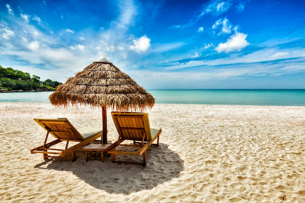 Twee ligstoelen onder tent op strand