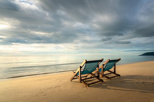Twee ligstoelen op het strand bij zonsondergang met een tropische zee