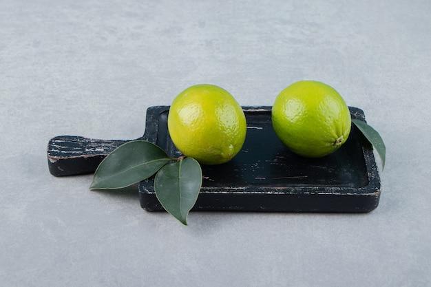Twee limoenvruchten met bladeren op snijplank.