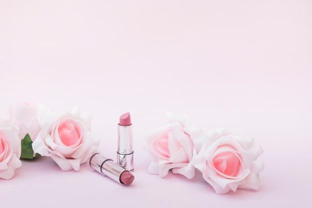 Twee lippenstiften en mooie rozen op roze achtergrond