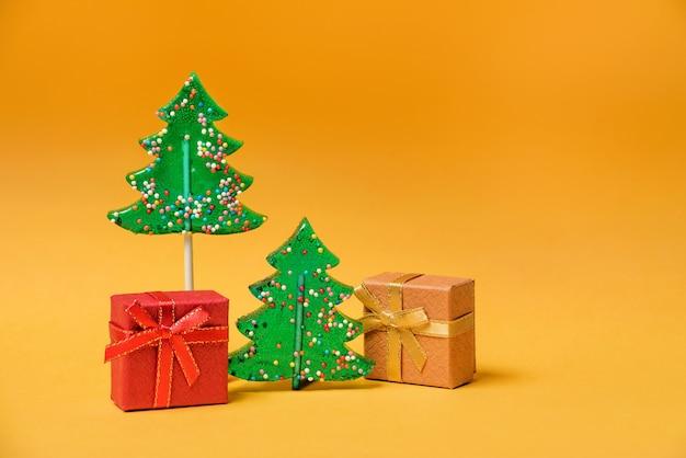 Twee lollies in de vorm van kerstbomen en dozen met geschenken op een gele achtergrond kopie ruimte.