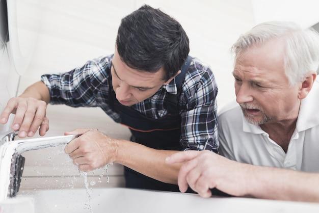 Twee loodgieters repareren de kraan in de badkamer