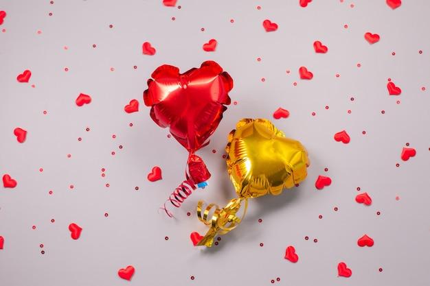 Twee luchtballonnen van hartvormig folie op feestelijk grijs.
