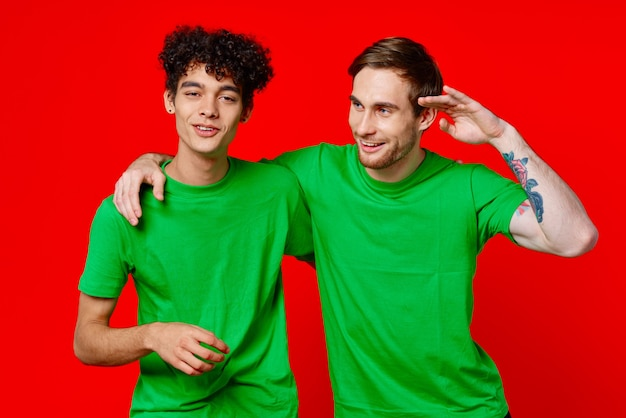 Twee man groene t-shirts omarmen emoties vriendschap rode achtergrond. hoge kwaliteit foto
