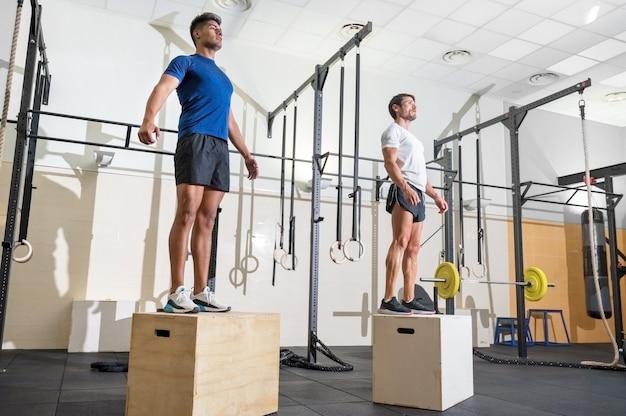 Twee man springen op fit box op sportschool