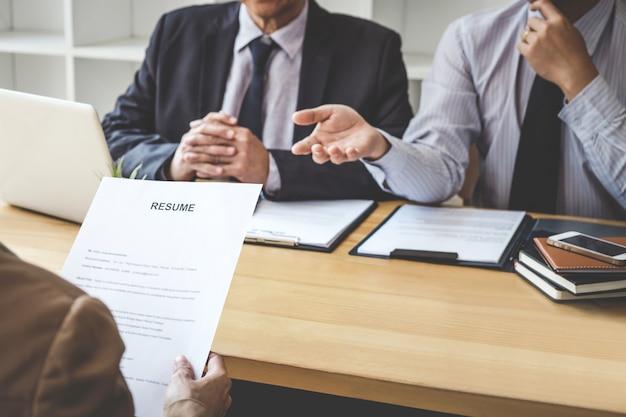 Twee manager stellen vragen aan sollicitant over werkgeschiedenis, colloquydroom, vaardigheid, expertise