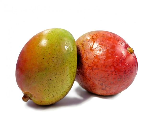 Twee mangovruchten sluiten samen geïsoleerd op een witte achtergrond.