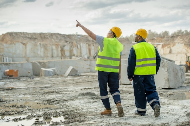 Twee mannelijke arbeiders in uniform bespreken kenmerken van bouwplaats