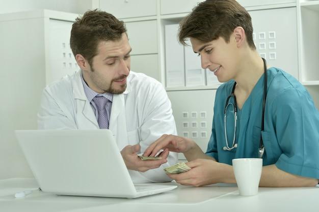 Twee mannelijke artsen met geld in medisch kantoor