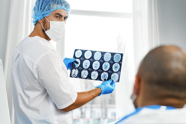 Twee mannelijke artsen onderzoeken mri-hersenscan van een patiënt in kabinet
