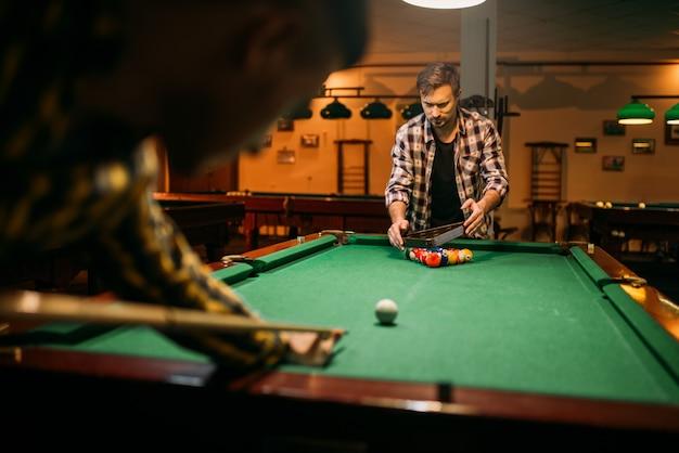 Twee mannelijke biljartspelers met richtsnoer aan de tafel