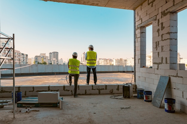 Twee mannelijke bouwers bij bouwwerf