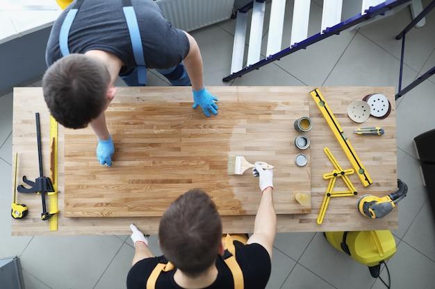 Twee mannelijke bouwvakkers bedekken de houten vloer met een beschermende vernislaag