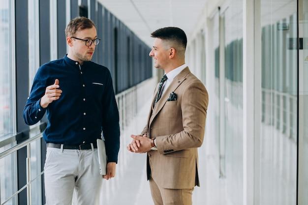 Twee mannelijke collega's op kantoor, die zich met laptop bevinden