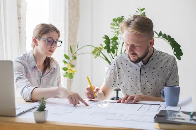 Twee mannelijke en vrouwelijke architect die aan blauwdruk op het kantoor werken