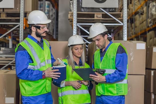Twee mannelijke en vrouwelijke werknemers die een beschermend uniform dragen, staan voor pakketten die naar het klembord kijken.