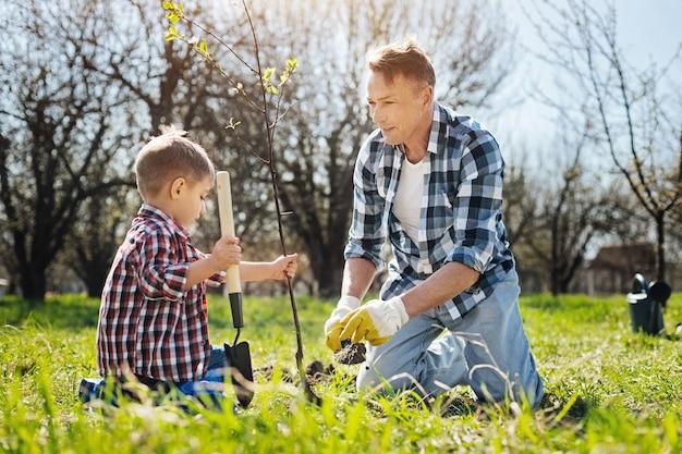Twee mannelijke familieleden werken buiten samen en bedekken de graszoden met een compost met behulp van grondlepels