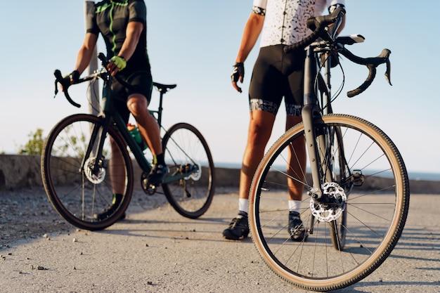 Twee mannelijke fietsers staan op de kustweg en rusten uit