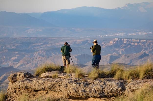 Twee mannelijke fotografen die foto's van de gorafe-woestijn nemen in het licht van de zonsondergang