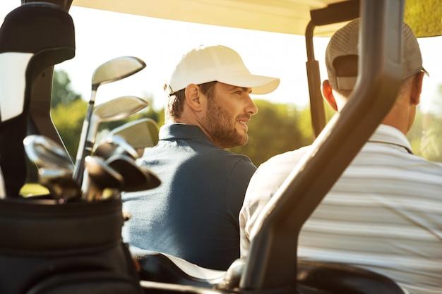 Twee mannelijke golfers zitten in een kar