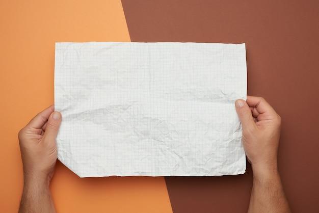Twee mannelijke handen houden een blanco verfrommeld vel wit papier vast