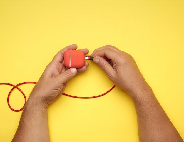 Twee mannelijke handen houden een kabel en een rode doos met draadloze koptelefoons, gele tafel, bovenaanzicht