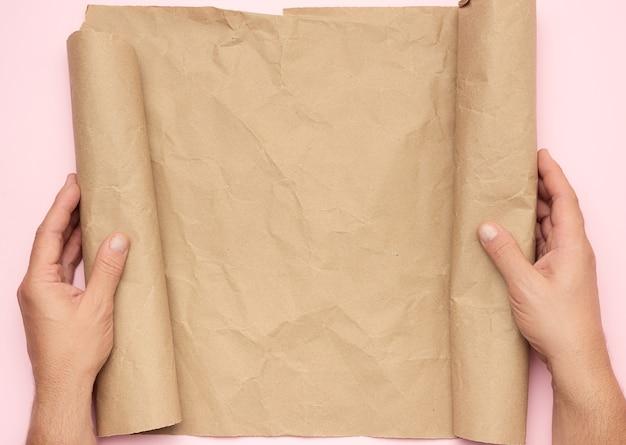 Twee mannelijke handen houden een rol bruin papier vast, kopie ruimte